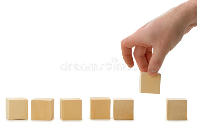 The Hand Establishes A Wooden Cube In Row Stock Photography