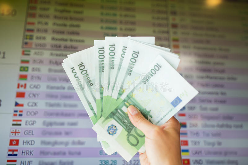 Hand with euro money over currency exchange rates stock photo