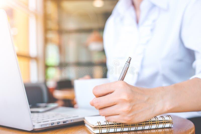 Hand för affärskvinna genom att använda bärbara datorn och skriva i notepad med ett p royaltyfri bild