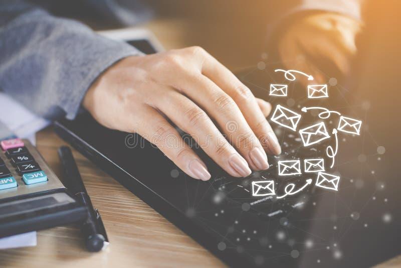 Hand för affärskvinna som arbetar på datorbärbara datorn som överför emailen arkivbild