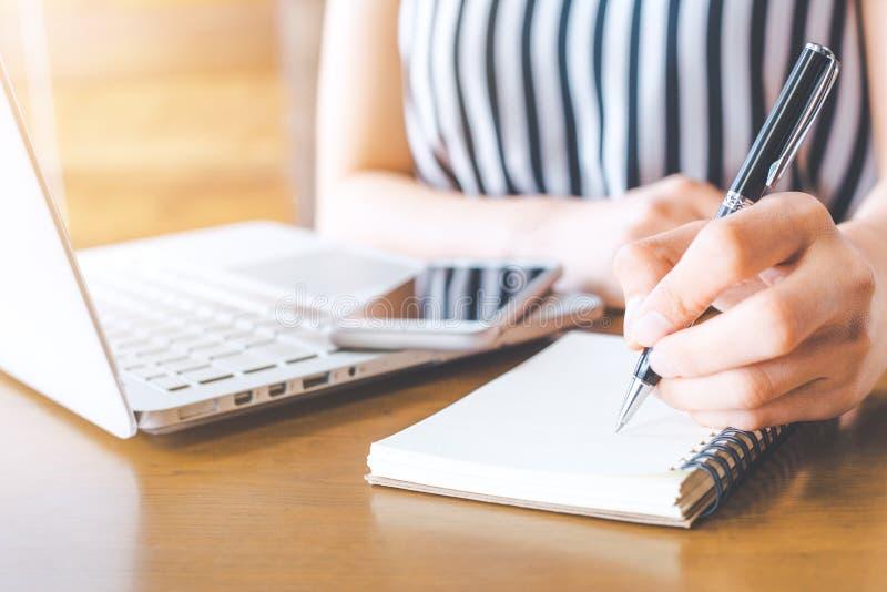 Hand för affärskvinna som arbetar på en dator och skriver på en notep arkivfoton