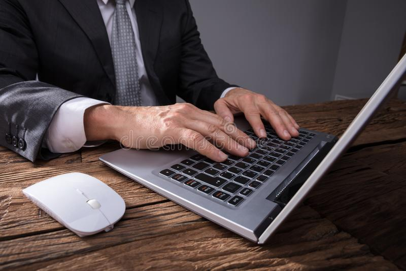 Hand för affärsman` s genom att använda bärbara datorn royaltyfria foton