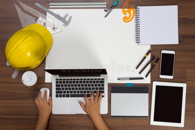 Hand för bakgrund för kontorsskrivbord genom att använda ett bärbar datorkonstruktionsprojekt royaltyfri foto