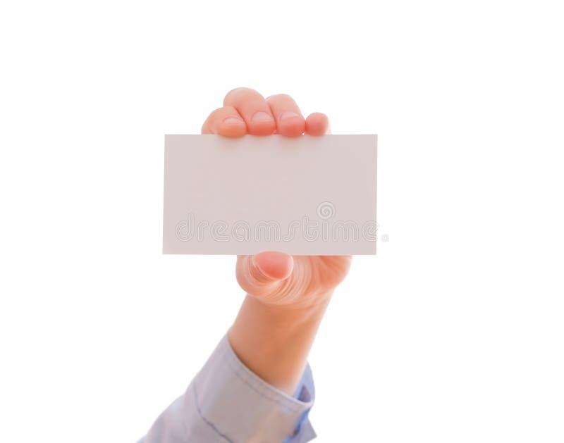 Hand för barn` som s visar ett tomt affärskort arkivbild