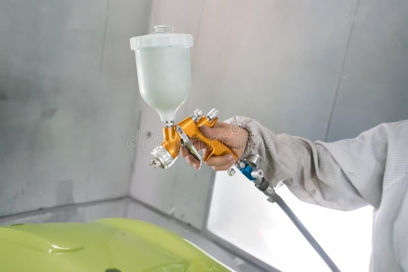 Hand för bilrepairmanmålare i skyddande handske med airbr royaltyfria bilder