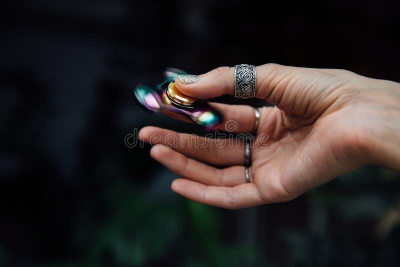 Hand för flicka` s med rastlös människaspinnaren Rymmer en skinande metallisk handspinnare Hippier och Bohemia royaltyfri fotografi