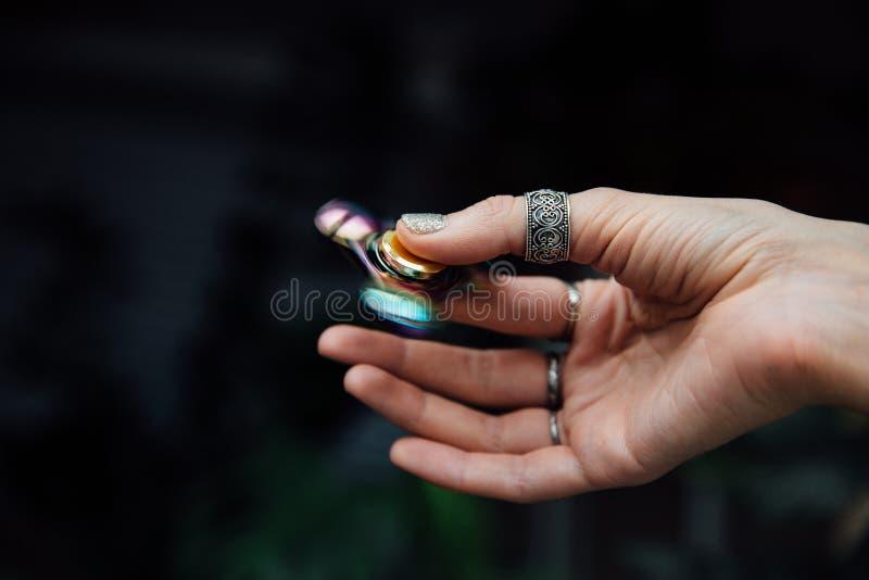 Hand för flicka` s med rastlös människaspinnaren Rymmer en skinande metallisk handspinnare Hippier och Bohemia fotografering för bildbyråer