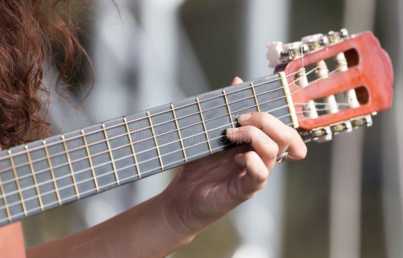 Hand för flicka` som s spelar gitarren arkivfoto