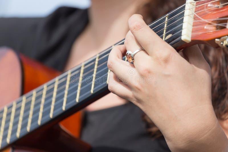 Hand för flicka` som s spelar gitarren arkivbild