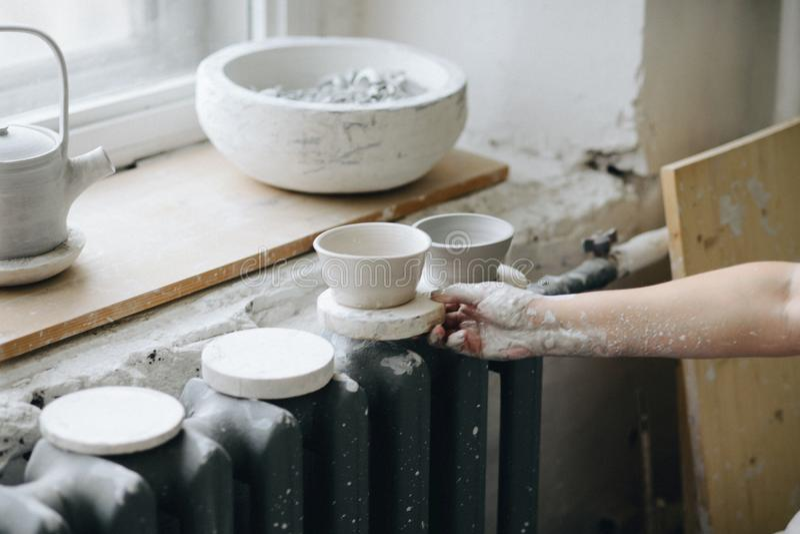 Hand för kvinna` s med den keramiska bunken på krukmakeristudion arkivfoton