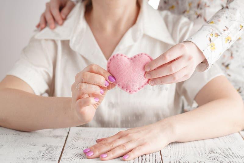Hand för kvinna` som s rymmer handen för barn` s med en hjärta Begreppet av moderskap som att bry sig, familj, skydd, förälskelse arkivfoto