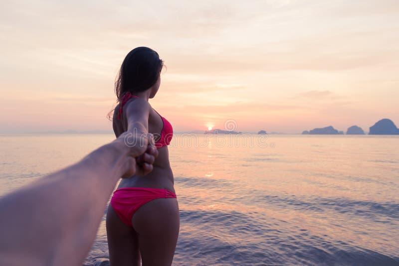 Hand för kvinnahållman som går på stranden på solnedgången, ungt turist- par på havsferie arkivfoto