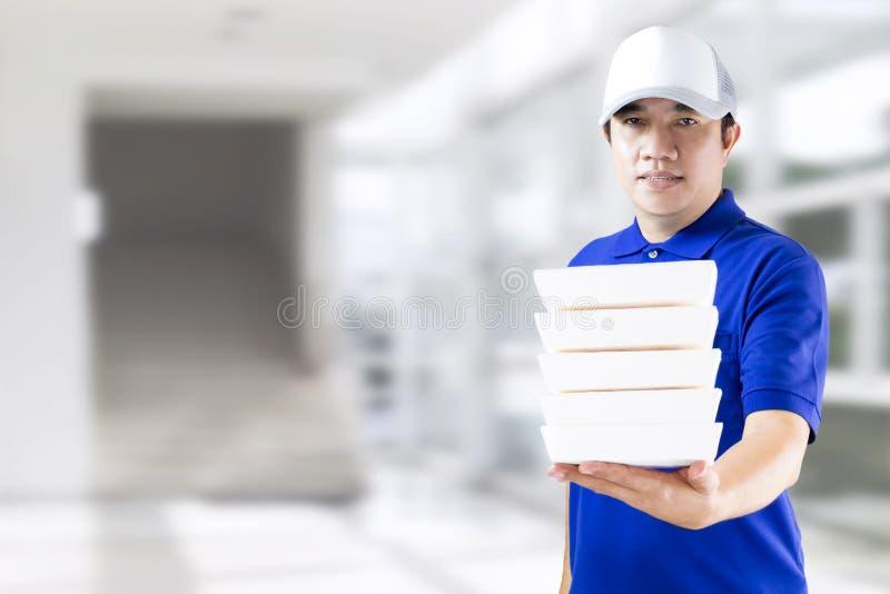 Hand för leveransman som rymmer att förpacka för snabbmat i blå likformig Mathemsändning- eller beställningsmatonline-begrepp Aff royaltyfria foton