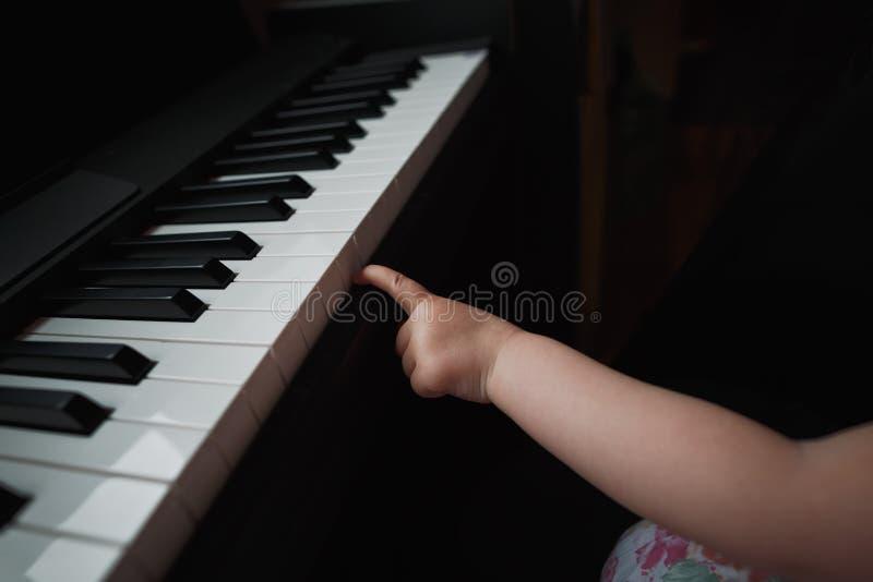 Hand för liten flicka` s bredvid pianot Ett litet finger försöker att trycka på tangenterna Ingen framsida close upp arkivbild