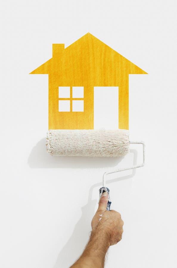 Hand för målarfärgrulle med gul hussymbolmålning på väggisolator fotografering för bildbyråer