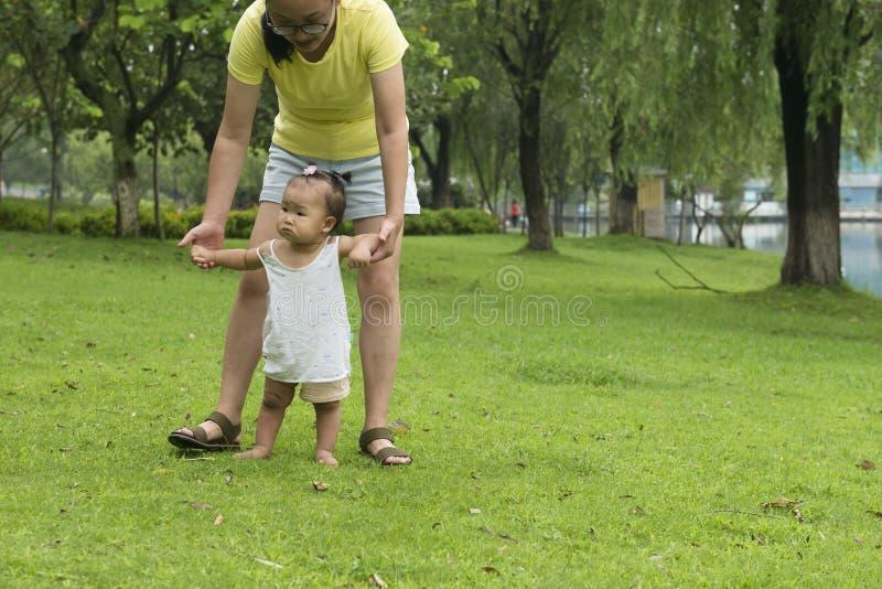Hand för mammahålldotter som hjälper lilla barnet att gå royaltyfri foto