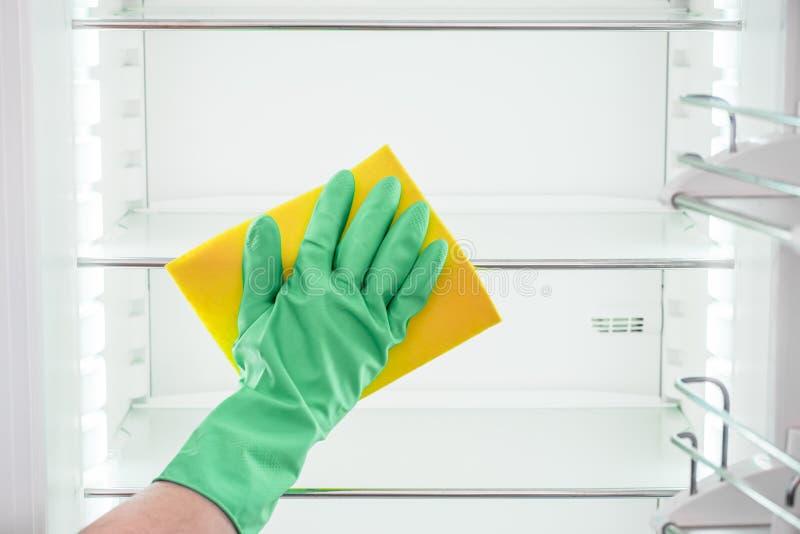 Hand för man` s i den gröna handsken som gör ren det tomma kylskåpet royaltyfri fotografi