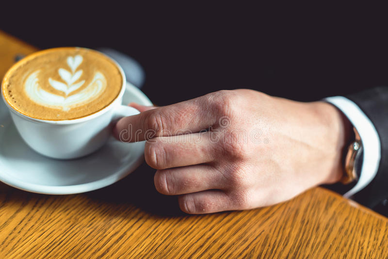 Hand för man` s i en dräkt som rymmer en kopp kaffe royaltyfria foton