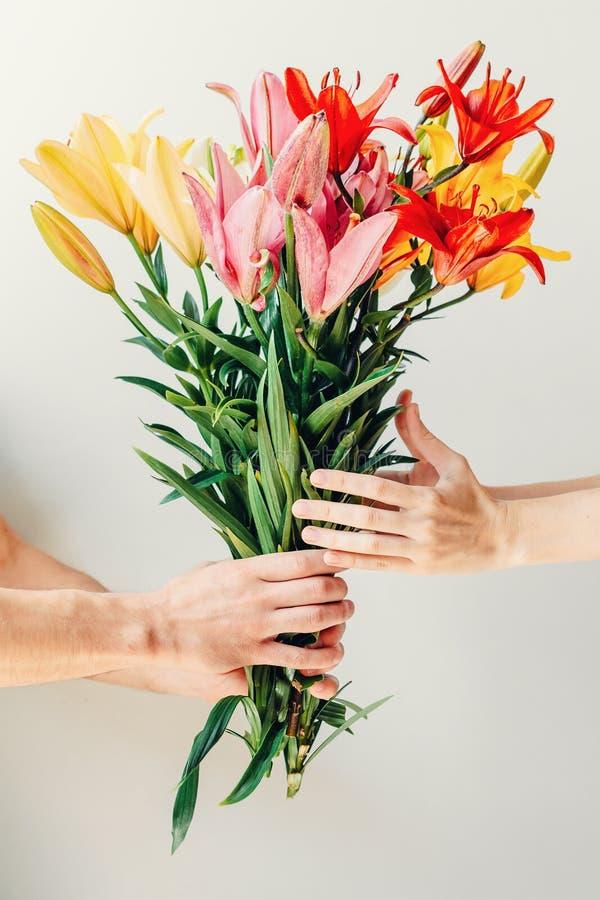 Hand för man` som s ger buketten av blommor till handen för woma` s på vit bakgrund arkivfoton