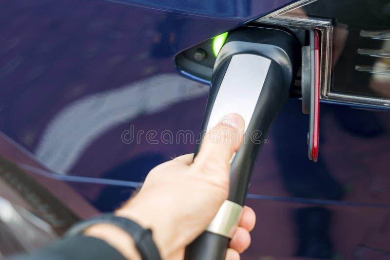 Hand för man` som s rymmer modernt elbiluppladdareuttag arkivfoto