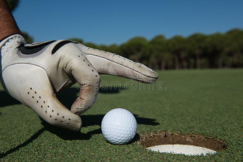 Hand för man` som s sätter golfboll i hål royaltyfria foton