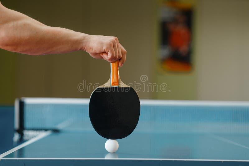 Hand för manlig person med racket och att knacka pongbollen arkivbilder