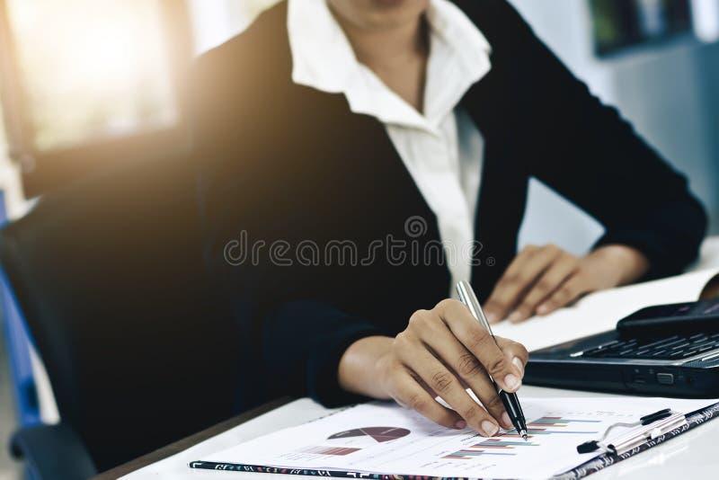 Hand för närbild för affärskvinnor med pappers- handstil på grafen royaltyfri fotografi