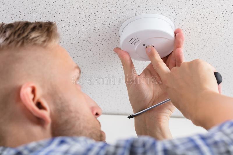 Hand för person` som s installerar rökavkännaren på tak arkivfoton