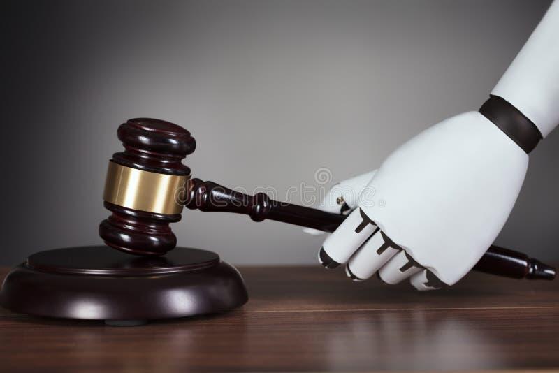 Hand för robot` som s slår auktionsklubban på skrivbordet royaltyfria bilder