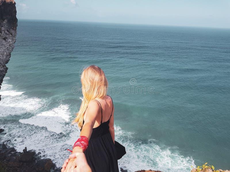 Hand för ` s för pojkvän för tillbaka siktskvinna hållande över hav- och himmelbakgrund royaltyfri foto