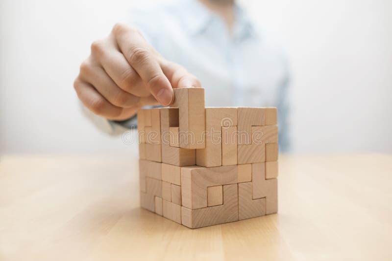 Hand f?r man` som s tillfogar det sista saknade tr?kvarteret in i st?lle royaltyfria foton
