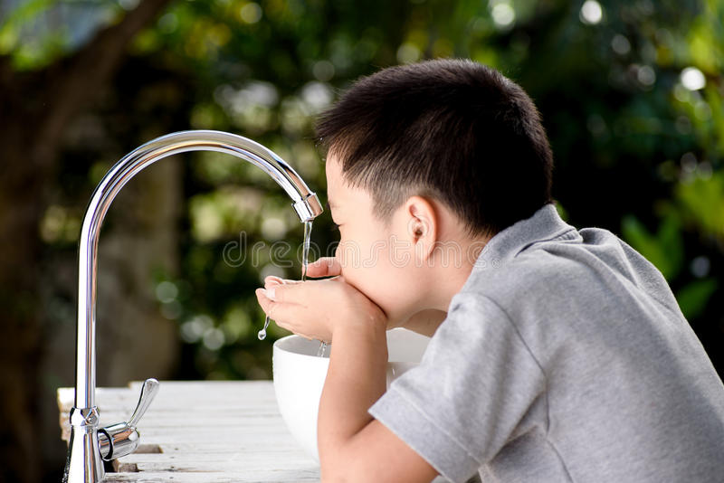 Hand and faucet. Close up kid hand under the brand new faucet royalty free stock images