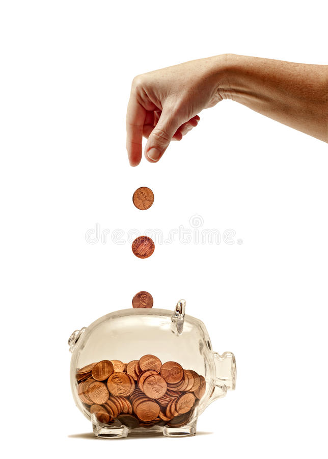 Hand dropping pennies into piggy bank royalty free stock photography
