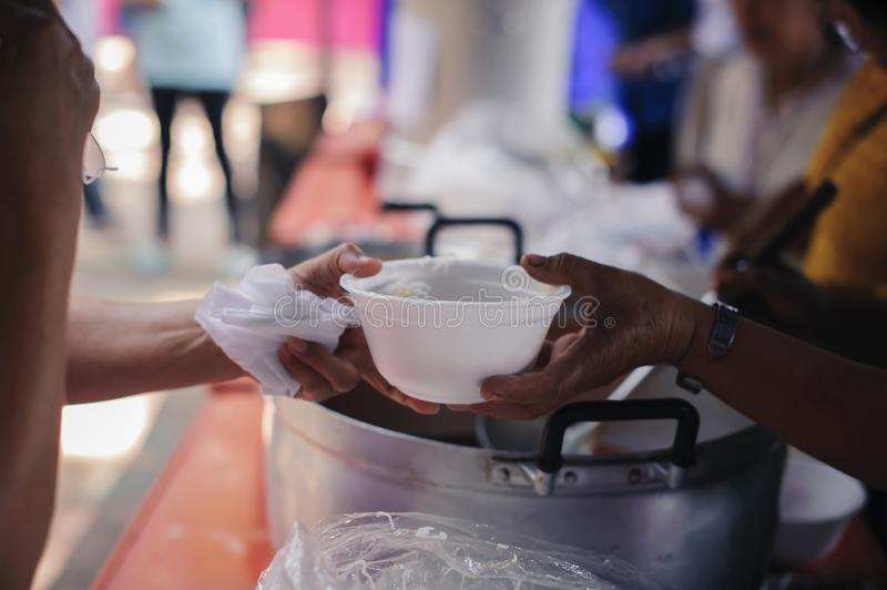 Hand-feeding to the needy in society : Concept of Feeding : Volunteers give food to the poor : donating food is helping human stock images