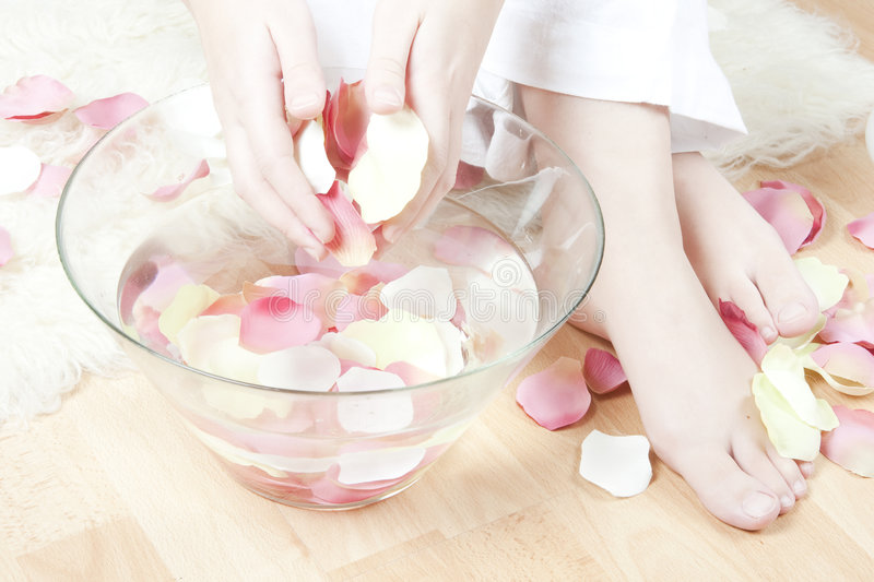 Hand and feet spa. Woman hands and feet, rose petals spa