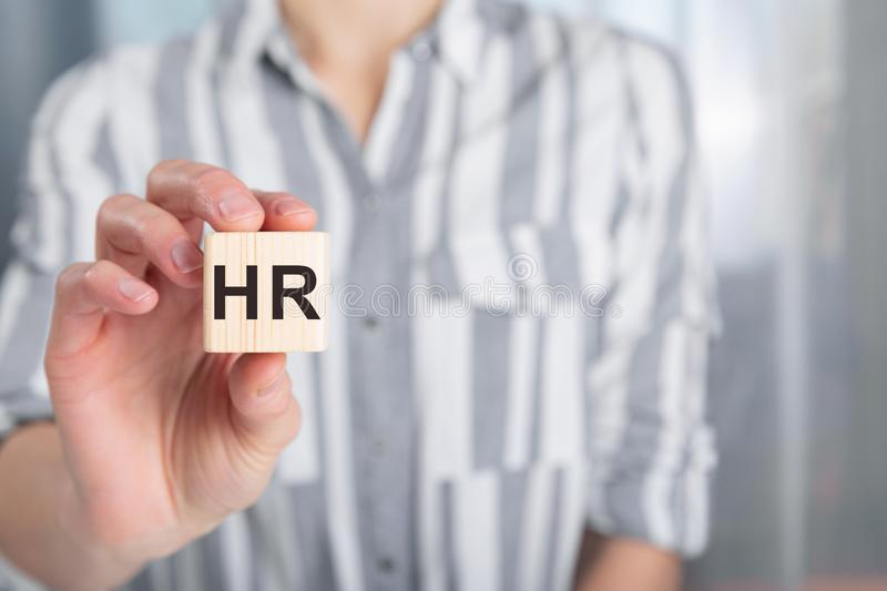 Hand of female holding wood cube block with letters HR. Human Resources and personnel hiring concept. In a natural light stock image
