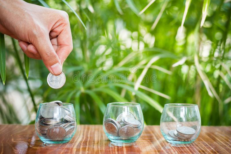 Hand of female putting coins in jar with money stack step growing growth saving money stock photo