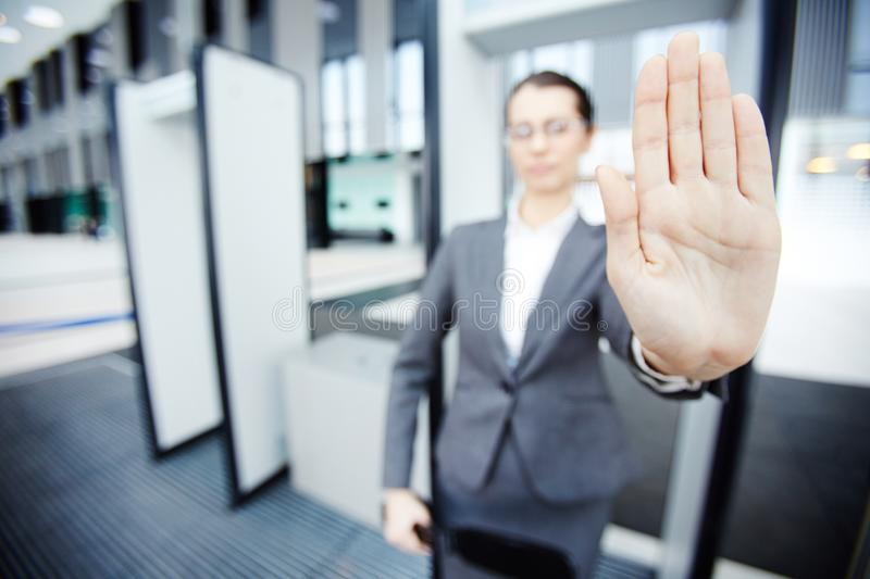 Stop here. Hand of female security showing stop gesture to someone while standing by gates in airport entrance royalty free stock images