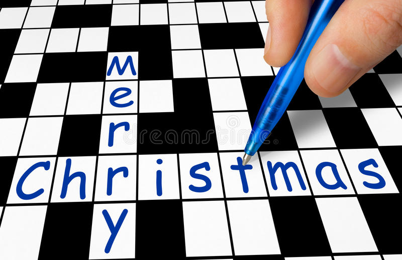 Hand filling in crossword - Merry Christmas royalty free stock photos