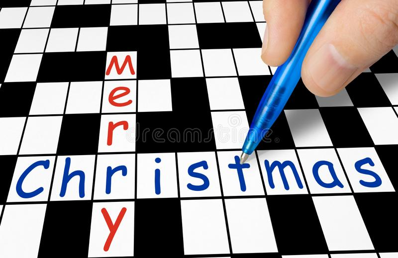 Hand filling in crossword - Merry Christmas royalty free stock image