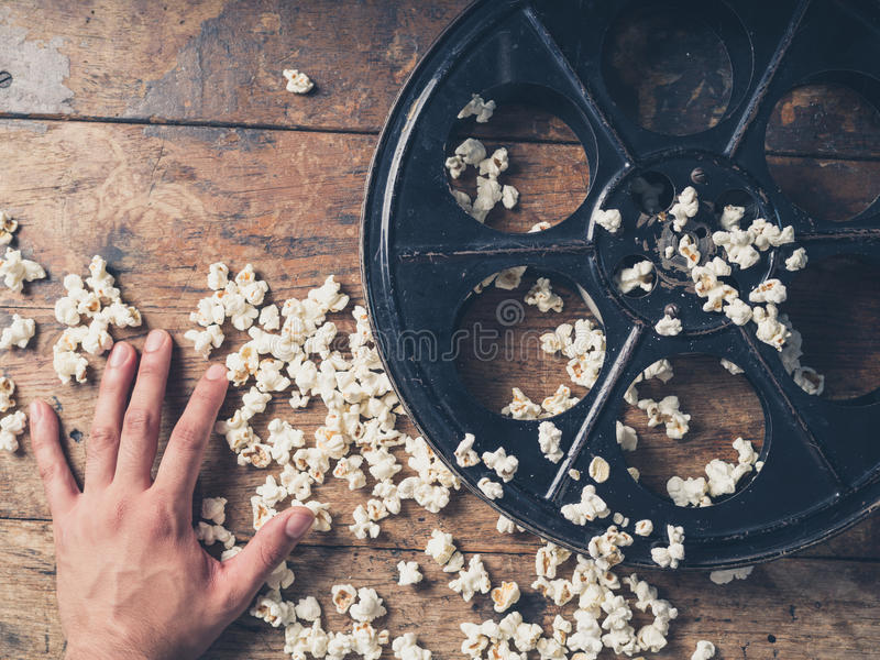 Hand with film reel and popcorn stock images