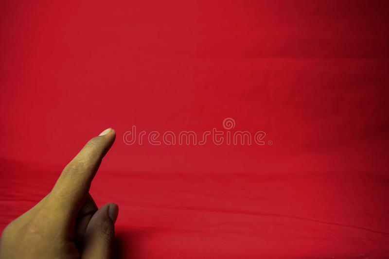 Hand with finger held up on the red background royalty free stock photos