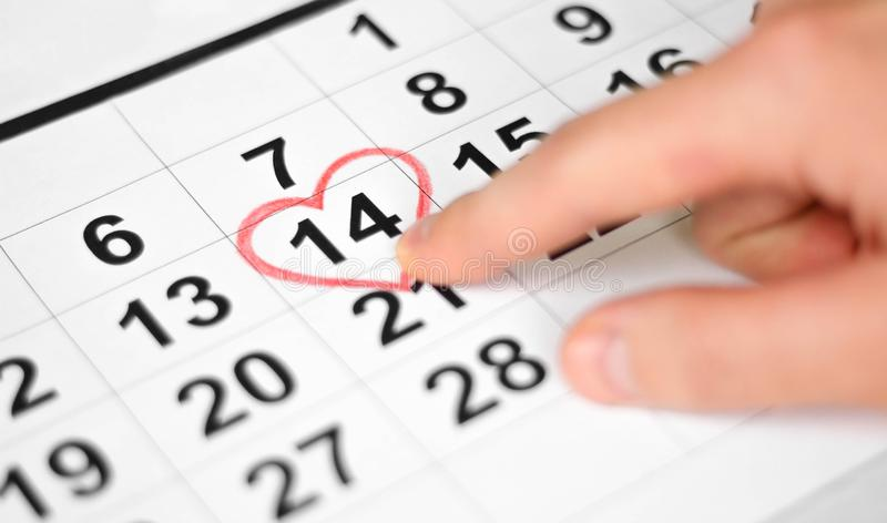Hand finger pointing to February 14th. Calendar sheet with 14th february date marked by red heart shape. Close up stock image