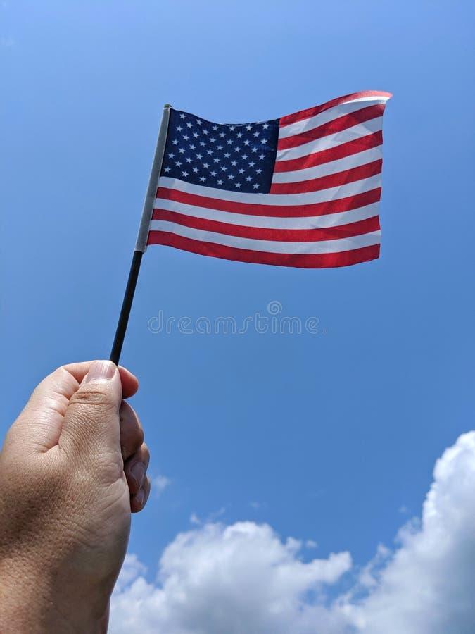 Hand-Flagge Vereinigter Staaten gegen sonnigen Sommernachmittagshimmel stockbild