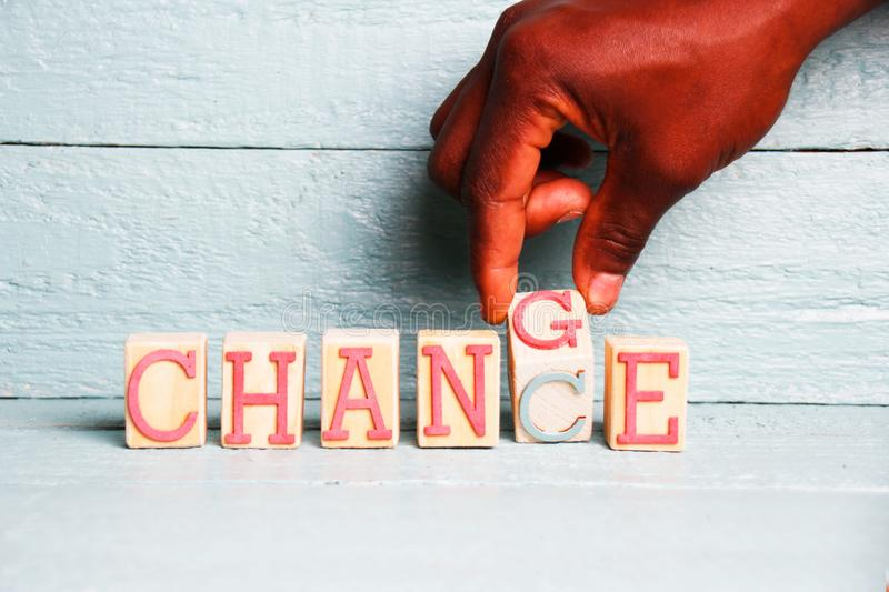 A hand flips a wooden cube with the words change into the word chance royalty free stock image