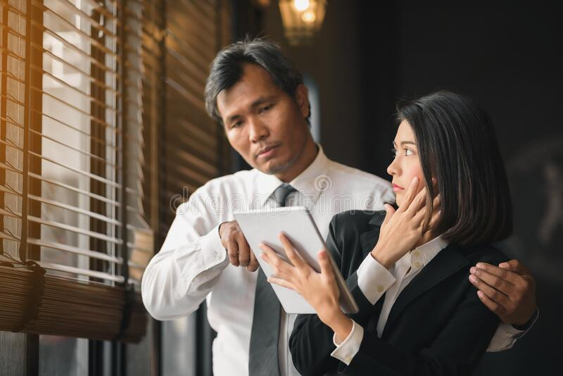 The hand of a flirtatious businessman is embracing his female secretary during counseling.  stock photo