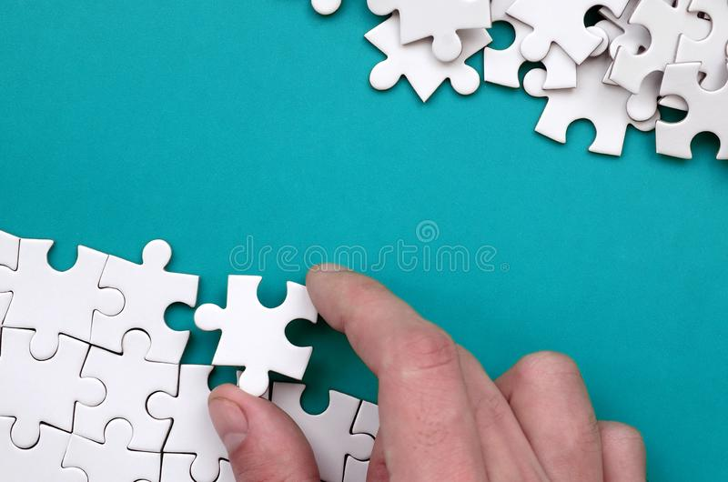 The hand folds a white jigsaw puzzle and a pile of uncombed puzzle pieces lies against the background of the blue surface. Texture royalty free stock photography