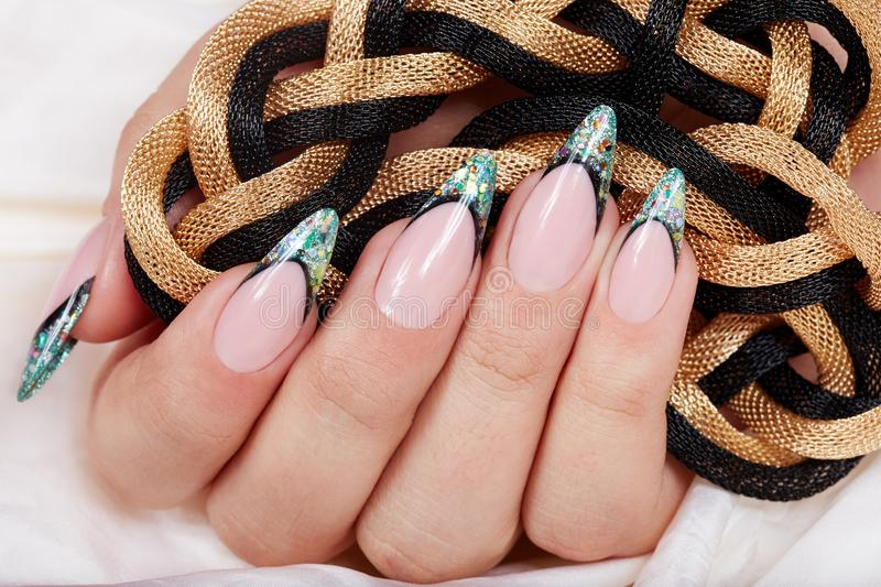 Hand with long artificial french manicured nails decorated with glitter. Hand with french manicured nails decorated with glitter holding a chain necklace royalty free stock photo