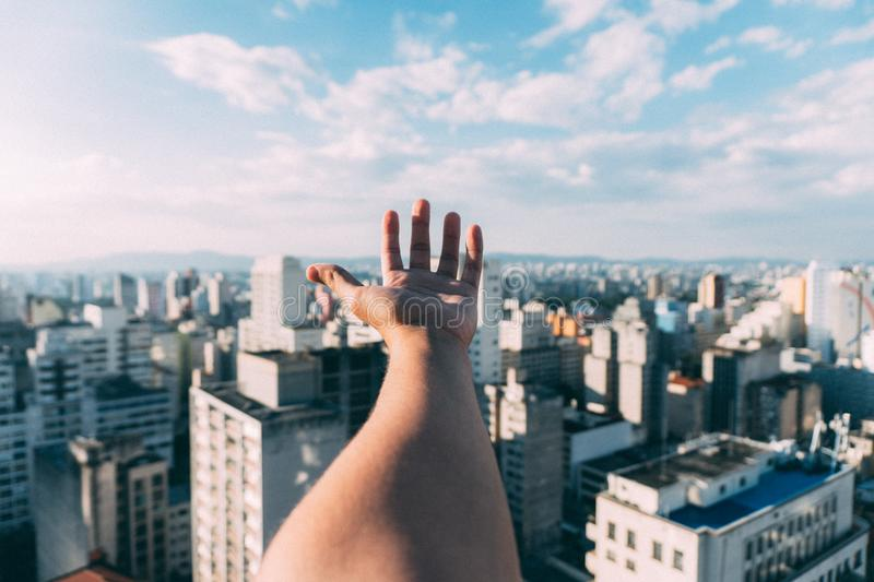 Hand in front of cityscape royalty free stock photo