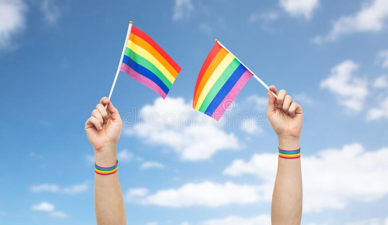 Hand with gay pride rainbow flags and wristbands stock photo